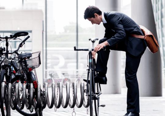 Mann i dress med skulderveske parkerer en sykkel ved kontorbygget