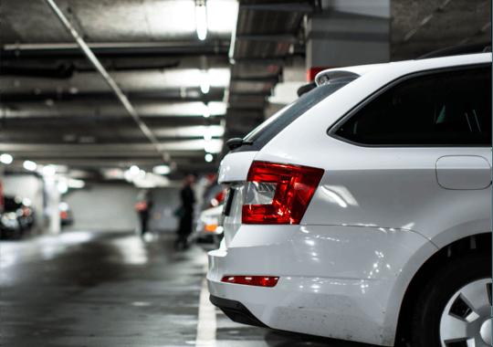 Baksiden av en hvit bil i en felles bilgarasje i kontorbygget