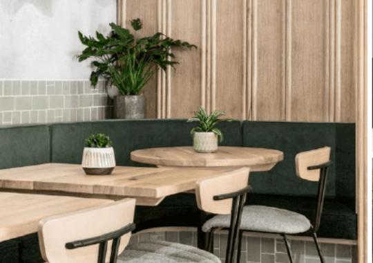 Sitteområde i en kafe preget av treverk og potteplanter
