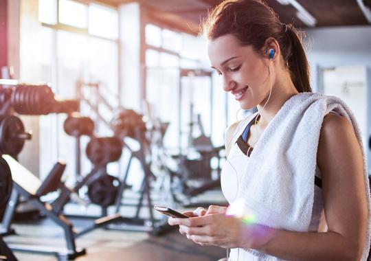 Smilende kvinne på treningssenter med et håndkle over skulderen og ser på mobilen sin
