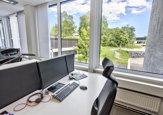 Dagens standard i kontorlokalene — kontorstol, skjerm og utsikt over parken